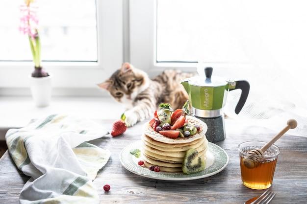 Pancakes con bacche fresche e miele e tè