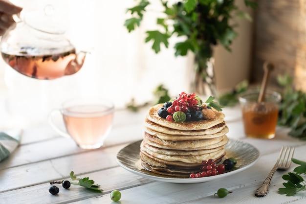 Pancakes con bacche fresche di lamponi, ribes, mirtilli, con miele e tè