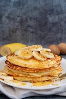 Frittelle con miele e banane su un piatto bianco con posto per il testo. colpo verticale