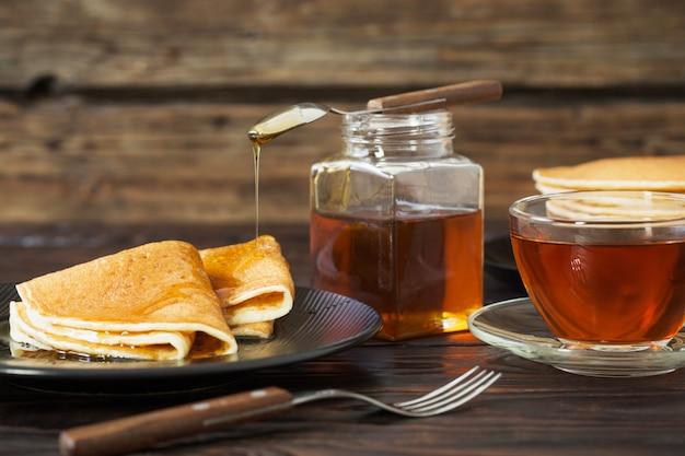 Pancake con miele e la tazza di tè sulla vecchia tavola di legno
