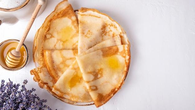 Frittelle con miele su un piatto. concetto di colazione del mattino. vista dall'alto, spazio di testo