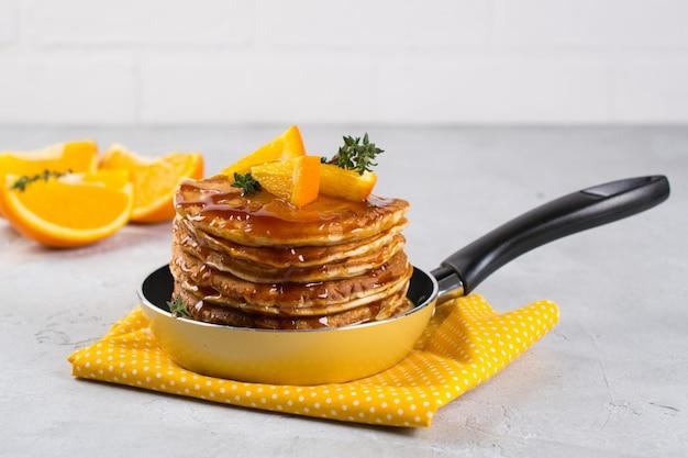 Pancake con lo sciroppo d'acero arancio e spruzzato in una piccola pentola gialla su superficie bianca. prima colazione