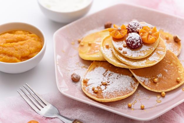 Frittelle con lamponi e zucchero a velo nel piatto rosa con forchetta, marmellata di mango, panna acida su bianco