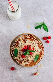Frittelle con lampone su fondo di pietra beige. frittelle fresche con mandorle e frutti di bosco. vista dall'alto