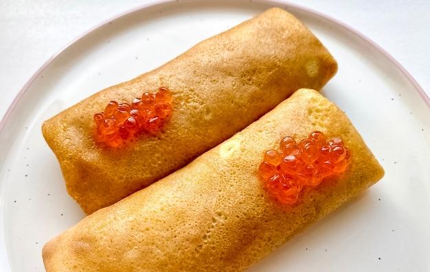Frittelle con caviale rosso su un piatto. avvicinamento. vista dall'alto