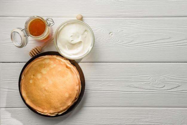 Frittelle con panna acida e miele sul tavolo