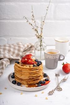 Frittelle con sciroppo e frutti di bosco su un tavolo per la colazione