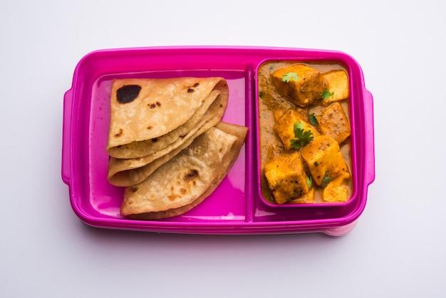 Paneer butter masala con roti in lunch box o tiffin, fuoco selettivo