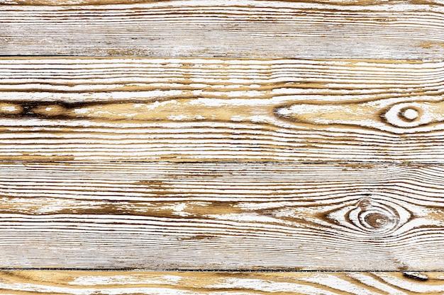 Pannello dalle vecchie, malandate tavole di colore chiaro con la fattura in legno brillantemente espressa.