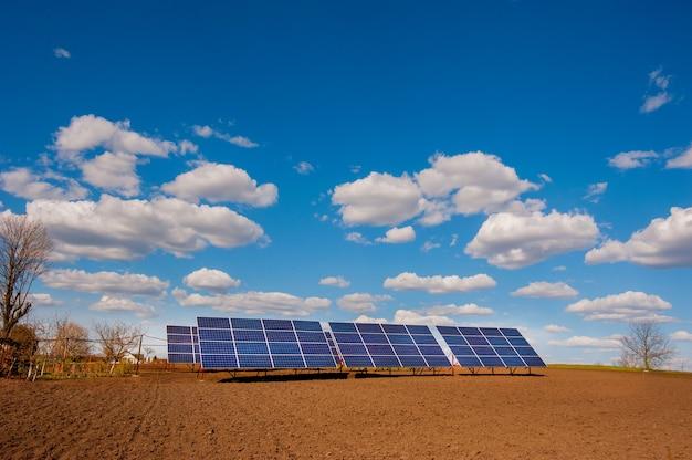 Sistema a pannelli di energia solare, vicino al terreno arato del campo primaverile e belle nuvole