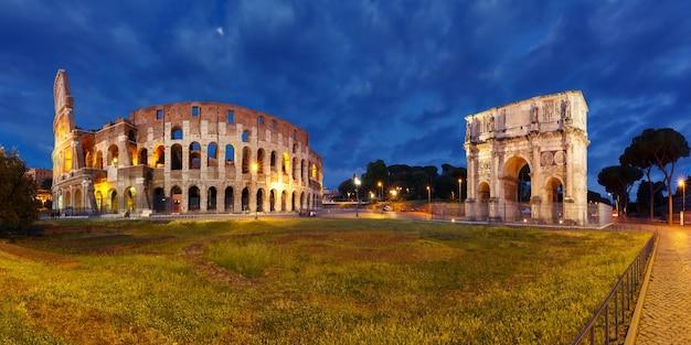 Panorama dell'arco di tito e colosseo o colosseo di notte, noto anche come anfiteatro flavio, il più grande anfiteatro mai costruito, nel centro della città vecchia di roma, italia.