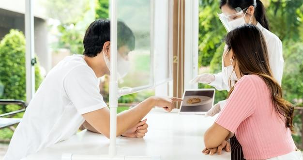 Panorama cameriera asiatica indossa maschera e visiera utilizzando il tablet per mostrare il menu elettronico del ristorante e consigliare ai clienti di coppia. nuova tecnologia normale e lifestyle food and dining concept.