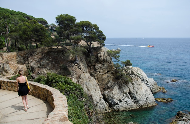 Panorama della strada delle belle rocce a lloret de mar e attraente giovane donna che cammina in abito nero e con una borsa gialla in cerca di un mare. la ragazza sta contro il mare e le rocce di rotolamento in spagna.