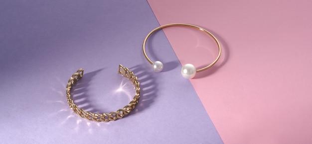 Panorama di bracciali a forma di catena e oro con perle su carta rosa e viola