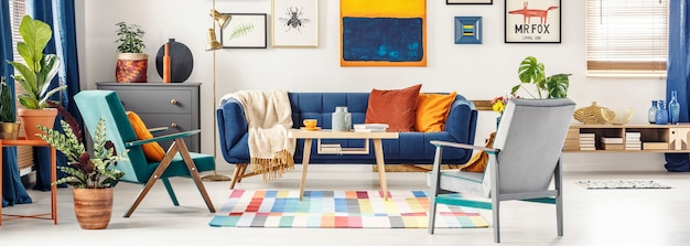 Panorama di un interno colorato soggiorno con una galleria di poster sulla parete bianca sopra un divano blu navy in piedi davanti a due poltrone vintage. foto reale