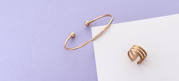 Panorama di oro con bracciale e anello di diamanti su sfondo bianco e viola con spazio di copia