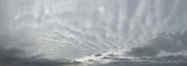 Panorama del cielo grigio drammatico con nuvole spesse ondulate.