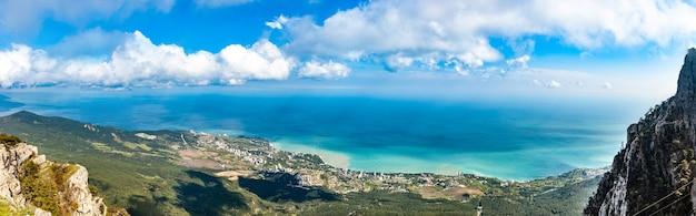 Panorama di colline e montagne e un villaggio costiero situato vicino al mare blu