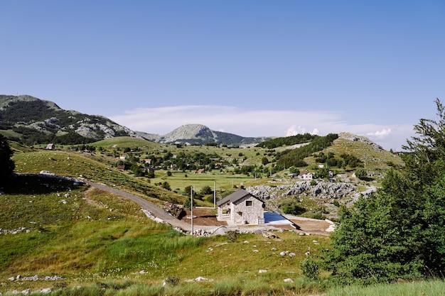 Panorama di una casa lungo la strada in un villaggio di alta montagna tra alberi, erbe e vegetazione