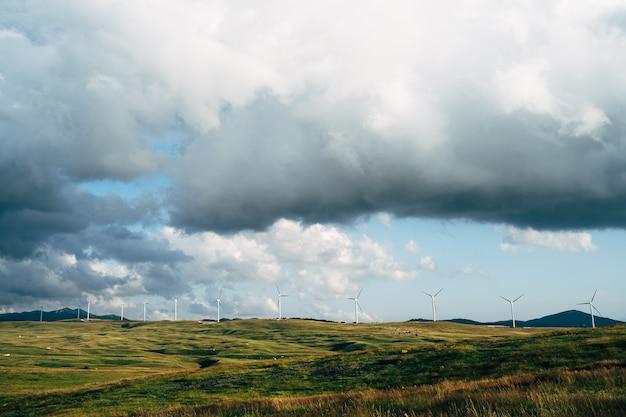 Panorama di molte enormi turbine eoliche sulla linea dell'orizzonte con cielo azzurro con nuvole tecnologia verde