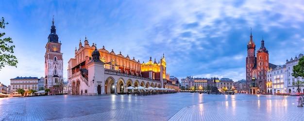 Panorama della piazza del mercato principale medievale con la basilica di santa maria, il palazzo del tessuto e la torre del municipio nel centro storico di cracovia al mattino