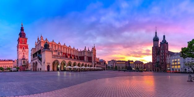 Panorama della piazza del mercato principale medievale con la basilica di santa maria, il palazzo del tessuto e la torre del municipio nel centro storico di cracovia all'alba