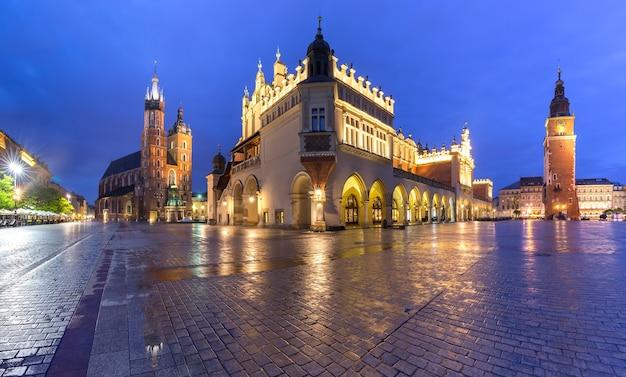 Panorama della piazza del mercato principale medievale con la basilica di santa maria, il palazzo del tessuto e la torre del municipio nel centro storico di cracovia