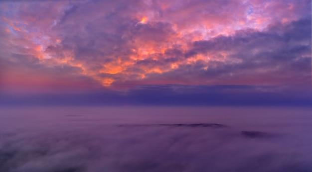 Panorama del cielo azzurro mattutino, illuminato dalla luce solare arancione e rossa, alba colorata.