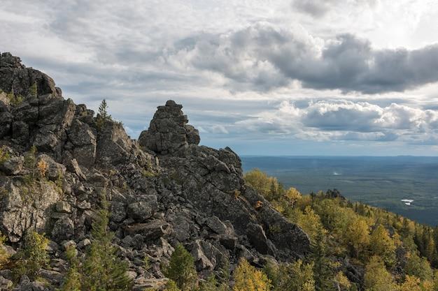 Panorama di scene di montagne nel parco nazionale kachkanar, russia, europa. tempo nuvoloso, cielo di colore blu drammatico, alberi verdi lontani
