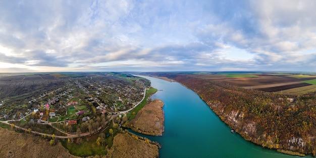 Panorama della natura in moldova. dniester con un villaggio sul lato del fiume, campi che si estendono all'orizzonte. vista dal drone