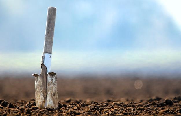 Panorama, vecchia pala sporca nel terreno su un campo arato