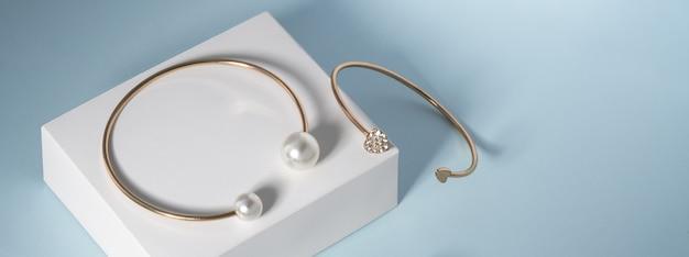 Panorama di braccialetto d'oro di perle e braccialetto d'oro di diamanti su sfondo bianco e blu con spazio di copia