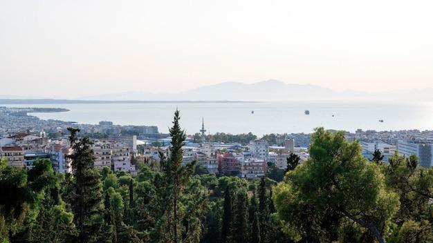 Panorama di salonicco in grecia da una collina, più edifici e il mare egeo in lontananza, verdi alberi in primo piano