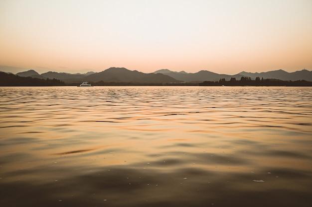 Scenario panoramico della scena nebbiosa nebbiosa della natura autunnale mattutina: foresta con alberi circondati da nebbia sulla superficie dell'acqua del lago con colline e