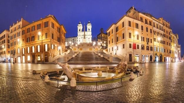 Panorama di scalinata piazza di spagna, piazza di spagna e la fontana del primo barocco chiamata fontana della barcaccia o fontana della brutta barca durante l'ora blu mattutina, roma, italia.