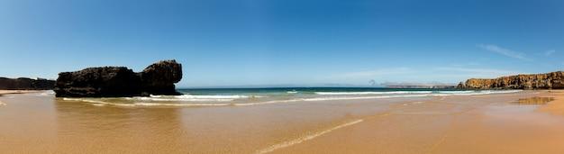 Panorama della spiaggia estiva con colline rocciose, portogallo