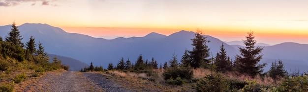Panorama del tramonto in montagne carpatiche con una strada sterrata di fronte