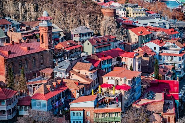Panorama delle case variopinte tradizionali con i balconi scolpiti colorati di legno e le mattonelle di tetto rosse nella vecchia città di tbilisi, georgia