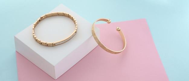 Panorama di due moderni braccialetti d'oro su sfondo di carta in colori pastello con spazio di copia