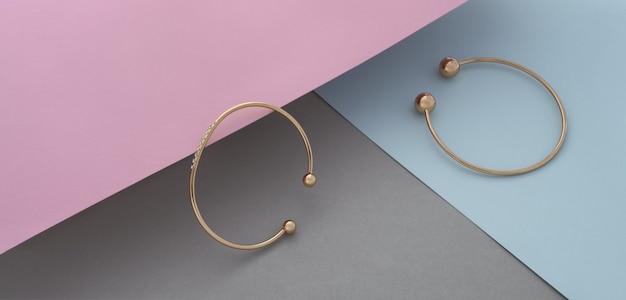 Panorama di due moderni braccialetti dorati con diamanti su sfondo color pastello con spazio copia