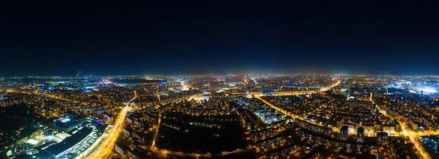Vista panoramica di bucarest di notte dal drone, più edifici residenziali e commerciali, molta illuminazione e lunga esposizione, romania