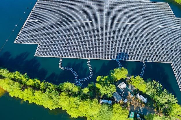 Vista panoramica su pannelli galleggianti sull'acqua con pannelli solari galleggianti in uno stagno blu sotto la luce del sole.