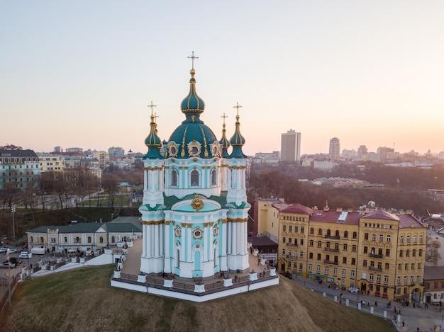 Vista panoramica di podol e la bellissima chiesa barocca di sant'andrea o la cattedrale di sant'andrea sul tramonto a kiev, ucraina. foto di drone