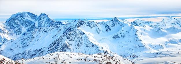 Panorama con gamma di picchi di montagne nella neve al tramonto