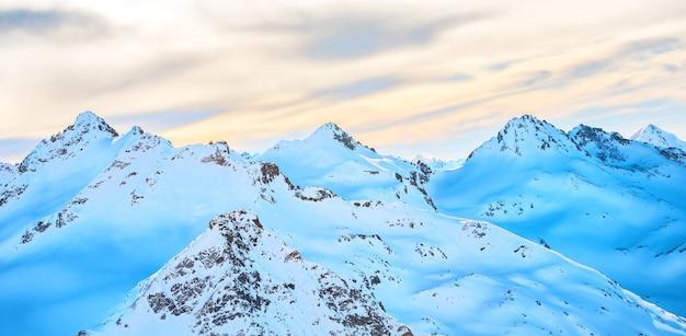 Panorama con paesaggio innevato in alte montagne blu in nuvole al tramonto