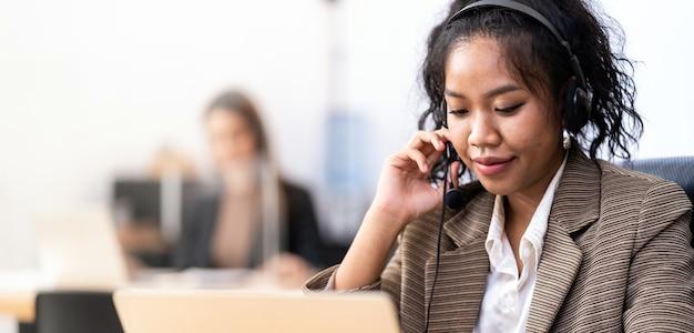 Panorama operatore di fiducia amichevole dei giovani adulti razza mista di donna asiatica africana con auricolari che lavorano in un call center