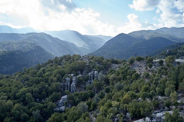 Vista aerea panoramica delle montagne e del cielo in una giornata estiva. vista di bellissime formazioni rocciose grigie tra alberi verdi.