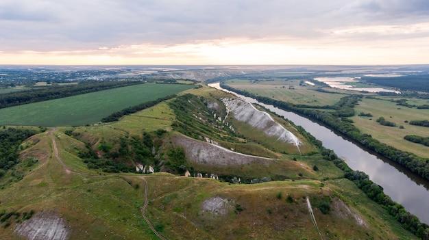 Vista aerea panoramica sopra la cima di un paesaggio estivo di un campo agricolo verde, colline o montagne, un grande fiume e una cintura forestale al tramonto