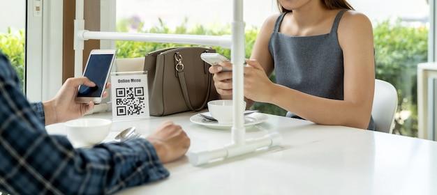I clienti asiatici panoramici scansionano il menu online del codice qr. Foto Premium