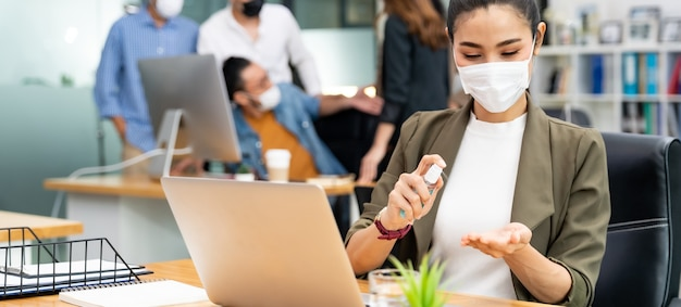 Panoramica asiatica dipendente ufficio imprenditrice indossare maschera viso utilizzare disinfettante per le mani spray alcol